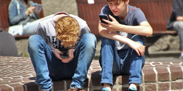 Kids sitting outside playing with their phones